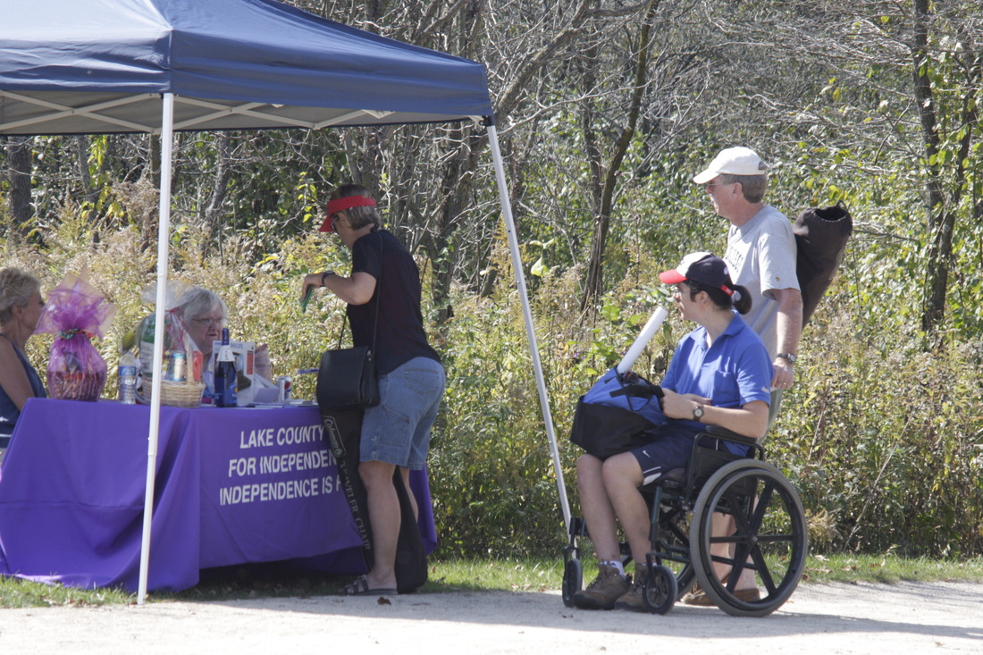 Photo of Wheel-a-Thon event of people signing up under a tent, in an outdoor wooded area. LCCIL is on a purple banner in front of a table.